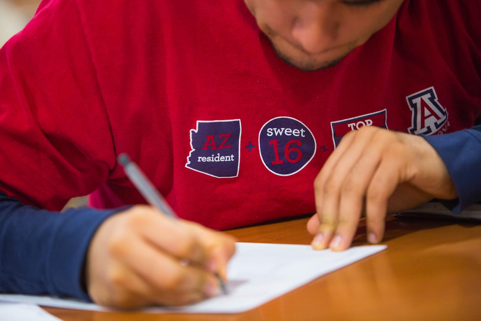 Student in red Arizona shirt writing